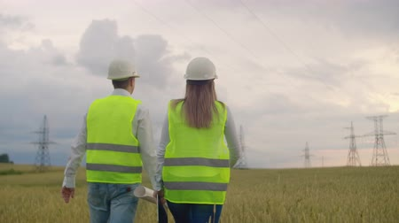 transformatör : An electrician in the fields near the power transmission line. The electrician manages the process of erecting power lines. The mechanic in a helmet. Stok Video