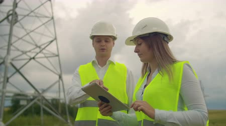 powerline : An electrician in the fields near the power transmission line. The electrician manages the process of erecting power lines. The mechanic in a helmet. Stock Footage