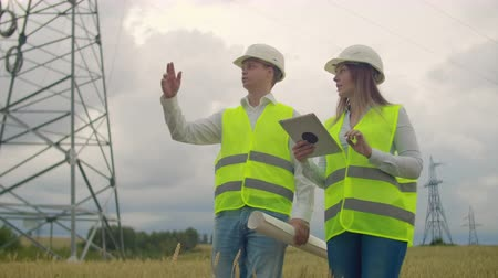 inspektor : Power lines, a man and a woman engineers with a tablet in their hands discussing the progress of the construction project.