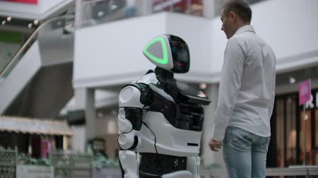 nobreza : A man in a shirt communicates with a white robot asking questions and pressing the screen with his fingers. Vídeos