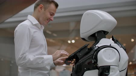 uznání : The man in the shopping Mall communicate with a robot Advisor. Modern shop and robot seller. Robot helps a man in the Mall
