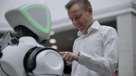 bot : A man in a shirt communicates with a white robot asking questions and pressing the screen with his fingers. Stock Footage