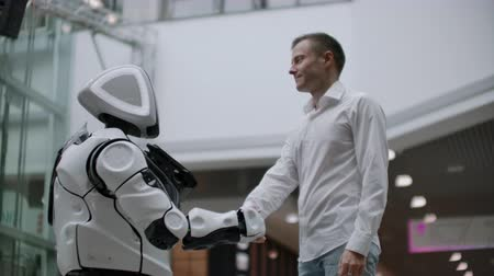 wynalazek : Interaction of man and modern technologies of artificial intelligence. Close up male hand of scientist shakes robotic arm. Robotic and human hands join in a handshake. Meeting and greeting friends