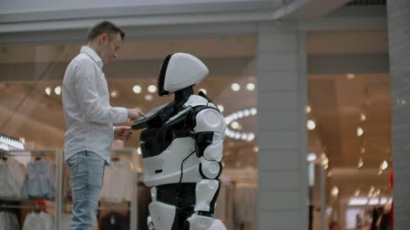 nobreza : A man stands with a robot bot and asks him questions and asks for help by clicking on the screen on the robot body. Vídeos