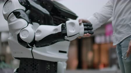 bezrobotny : Interaction of man and modern technologies of artificial intelligence. Close up male hand of scientist shakes robotic arm. Robotic and human hands join in a handshake. Meeting and greeting friends