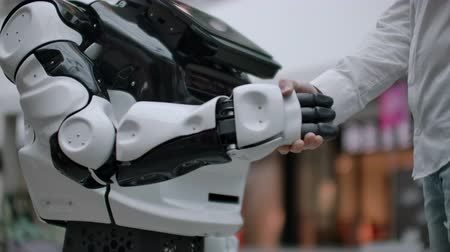 bezrobotny : Modern Robotic Technologies. A man communicates with a robot, presses a plastic mechanical arm to the robot, handshake Wideo