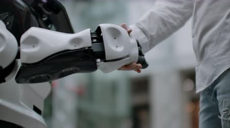nobreza : Hand of a businessman shaking hands with a Android robot. The concept of human interaction with artificial intelligence