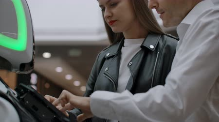 compreensão : The couple communicates with robot assistant with information screen in duty to give information. Contact with the robot and interaction with help systems