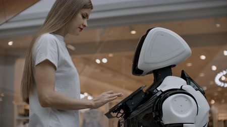 A female programmer tests the robot for the ability to interact with users. The use of a robot assistant in the office. The robot gives help to the girl.