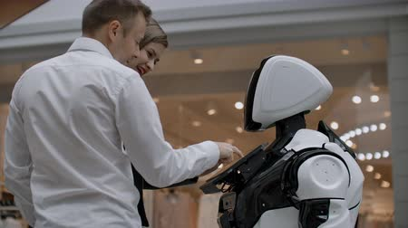 compreensão : Two people a man and a woman communicate with a robot. Press the robot with your hands on the screen. A robot assistant interacting in a shopping center with a couple.