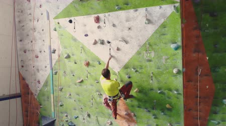 bouldering : Climber moves on the mountain in a room with a rope on the insurance and a bag for chalk overcoming the height rises to the top in slow motion.