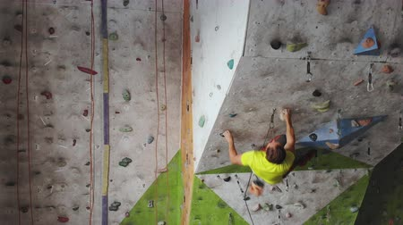 難しさ : Young man Rock climber is Climbing At Inside climbing Gym. slim pretty man Exercising At Indoor Climbing Gym Wall