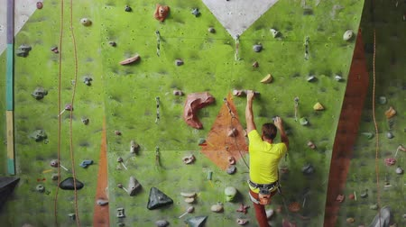 Male climber climbs the cliff wall in the room reaching and gripping hold. A professional concentrated climber moves up the wall, the camera rises and lays down his movements. Boom follow camera