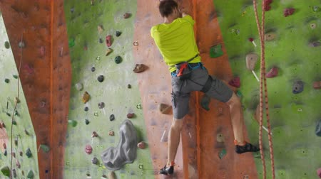 fearless : Climbing sport activity concept: Man climber on wall. Indoor climbing sport activity concept: man climber on artifical climbing wall Stock Footage