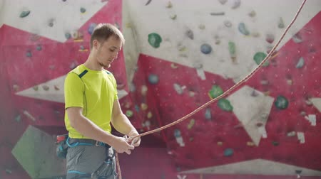 難しさ : Man belaying another climber on an indoor climbing wall