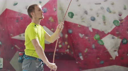 conquest : Close-up of Climber man belaying another climber against a wall with hooks. Stock Footage
