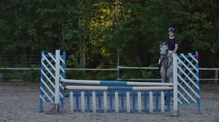 kötött : A woman jockey in a black and white suit on a horse makes a jump over the barrier. SLOW MOTION: A woman jockey in a black and white suit on a horse makes a jump.