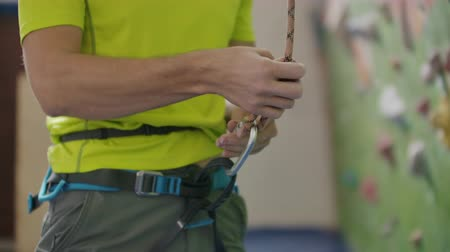 carabine : Climber attaching a belay rope and Chalking hands