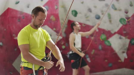 bouldering : Man belaying another climber on an indoor climbing wall