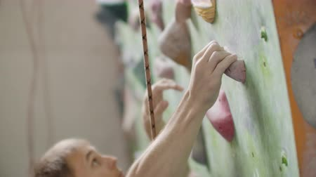 alpinism : Young man Rock climber is Climbing At Inside climbing Gym. slim pretty man Exercising At Indoor Climbing Gym Wall