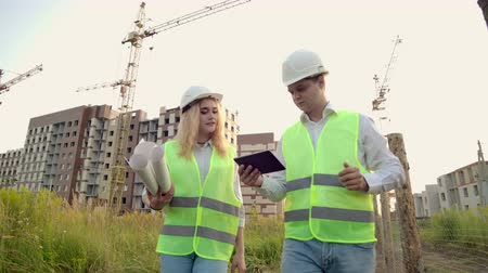 estocolmo : A man and a woman in protective clothing and helmets go to the construction site to discuss and look around click on the tablet screen on the background of working cranes