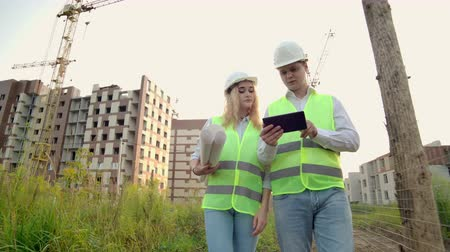 stockholm : Business, building, industry, technology and people concept - smiling builder in hardhat with tablet pc computer along with woman with drawings of builders at construction site.