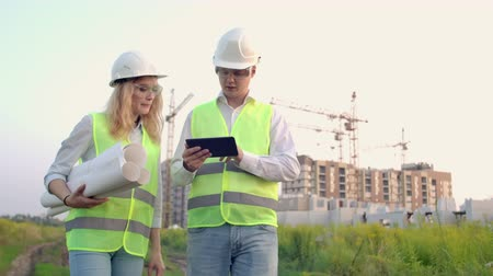 инспектор : Adult engineer man and architect woman uses a tablet in operation. Writes a message or checks a drawing. Against background is building.