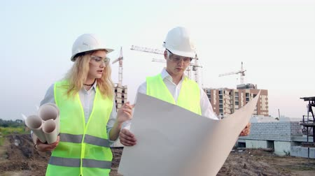 inspektor : The builder and architect man and woman are discussing the construction plan of the modern business center standing near construction site. They go to the building