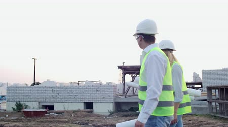 estocolmo : Man and woman supervisor and assistant with drawings in white helmets go and talk on the construction site showing the location of objects