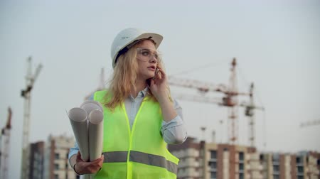 felügyelő : Portrait of a woman engineer in a helmet talking on the phone on the background of construction with cranes holding drawings in his hands. Female engineer on construction site