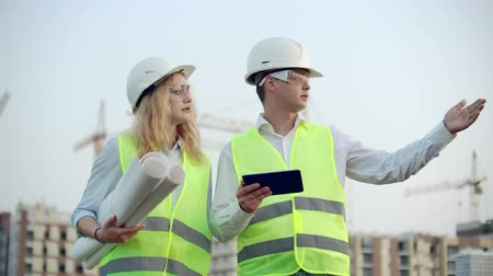 kompakt : Two industrial engineer wear safety helmet and holding tablet engineering working and talking with drawings inspection. On building outside. Engineering tools