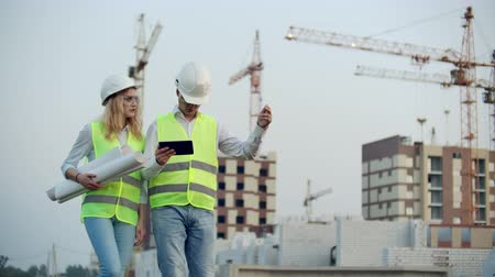 compacto : Two industrial engineer wear safety helmet and holding tablet engineering working and talking with drawings inspection. On building outside. Engineering tools