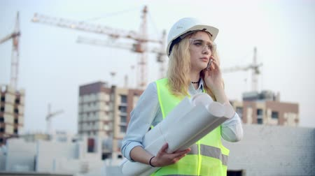 regisseur : Woman engineer designer talking on the phone with the contractor with drawings in hand on the background of buildings under construction and cranes.