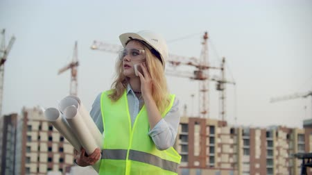 scheidingslijnen : Woman engineer designer talking on the phone with the contractor with drawings in hand on the background of buildings under construction and cranes.