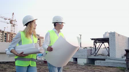workgroup : Man engineer and woman architect at a construction site. Building, development, teamwork and people concept. Man engineer and women architect at a construction Stock Footage