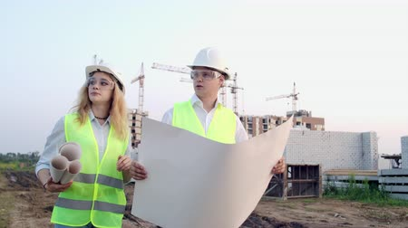 přímý : Workers with drawings at the construction site. Two workers man and woman in protective harhats working with drawings at the construction site outdoors