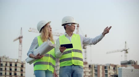 felügyelő : Two colleagues of engineers a man and a woman discussing a drawing and a tablet computer on the background of buildings under construction and cranes, a woman talking on the phone with the boss.