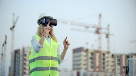 workman : Portrait of a female inspector analyzing the work of builders using virtual reality glasses. A woman in a helmet and a protective vest stands in VR glasses and moves his hands