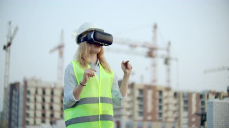 inspektor : Portrait of a female inspector analyzing the work of builders using virtual reality glasses. A woman in a helmet and a protective vest stands in VR glasses and moves his hands