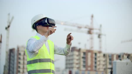 инспектор : Portrait of a male inspector analyzing the work of builders using virtual reality glasses. A man in a helmet and a protective vest stands in VR glasses and moves his hands