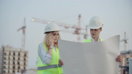 stockholm : Woman talking on the phone and asks the Builder what is on the drawings standing on the background of buildings under construction