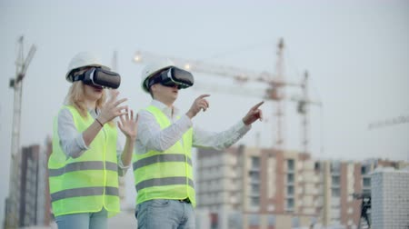 inspektor : Two people Man and woman wearing virtual reality glasses on the background of buildings under construction with cranes. Manager and assistant on design with your hands mimicking the interface Dostupné videozáznamy