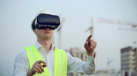 inspektor : Portrait of a male inspector analyzing the work of builders using virtual reality glasses. A man in a helmet and a protective vest stands in VR glasses and moves his hands