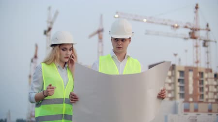 stoccolma : Two builders with drawings standing on the background of buildings under construction in helmets and vests, a woman talking on the phone with the customer