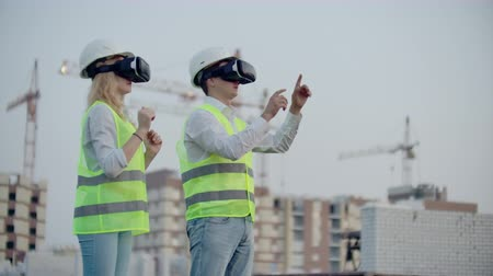 supervising : Two people in virtual reality glasses on the background of buildings under construction with cranes imitate the work of the interface for the control and management of construction