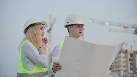 workgroup : Two builders with drawings standing on the background of buildings under construction in helmets and vests, a woman talking on the phone with the customer