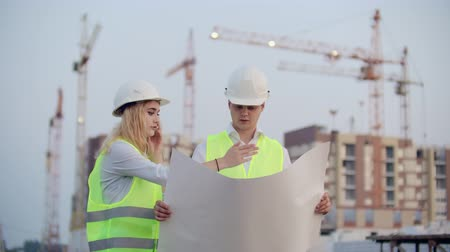 inspektor : Two colleagues engineers man and woman discussing the drawing on the background of buildings and cranes, a woman talking on the phone with the boss.