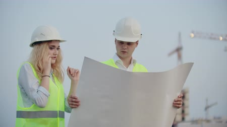 inspektor : Two builders with drawings standing on the background of buildings under construction in helmets and vests, a woman talking on the phone with the customer