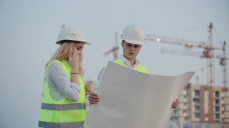 stoccolma : Woman talking on the phone and asks the Builder what is on the drawings standing on the background of buildings under construction