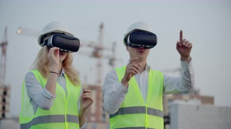 planlamacı : Two people in virtual reality glasses on the background of buildings under construction with cranes imitate the work of the interface for the control and management of construction